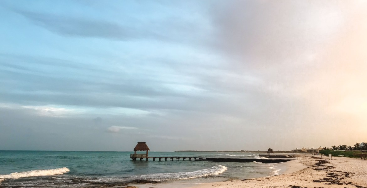 A small pier juts out into the Caribbean Sea between Mexico's Playa de Carmen and Cancún, at the Mayan Palace and Grand Mayan luxury resorts along the Riviera Maya. Clouds reflect the setting sun over the turquoise-blue water and white sand.