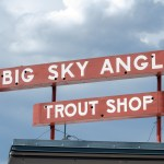 A commercial sign above the Big Sky Anglers Trout Shop in downtown West Yellowstone, Montana, near the West Gate Entrance to Yellowstone National Park and the borders of Idaho and Wyoming.
