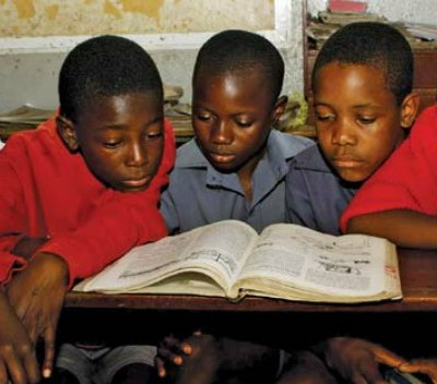 132630-004-281472B1 Students share a textbook at a primary school in Harare, Zimbabwe.