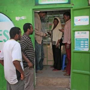 Kenyan customers make money transfers at an M-Pesa counter in Nairobi. Photo - AP - Sayyid Abdul Azim