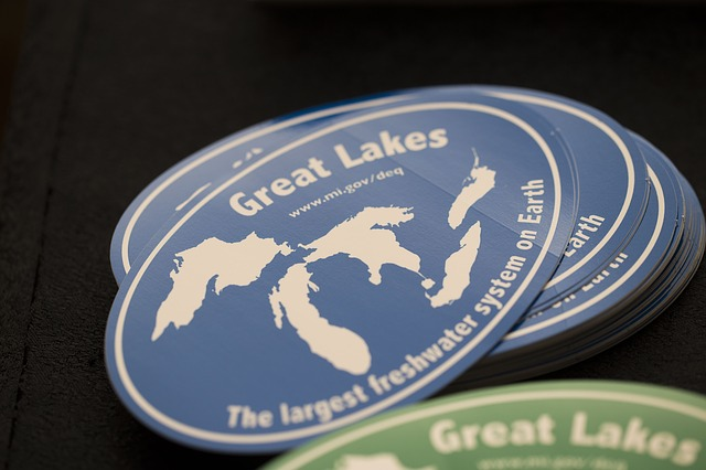 a small pile of oval stickers showing Michigan. Great Lakes www.mi.gov/