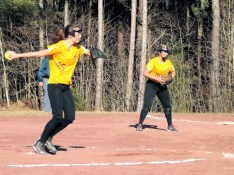 Jessica Gardinier firing a pitch with Amber Iannotti playing first base