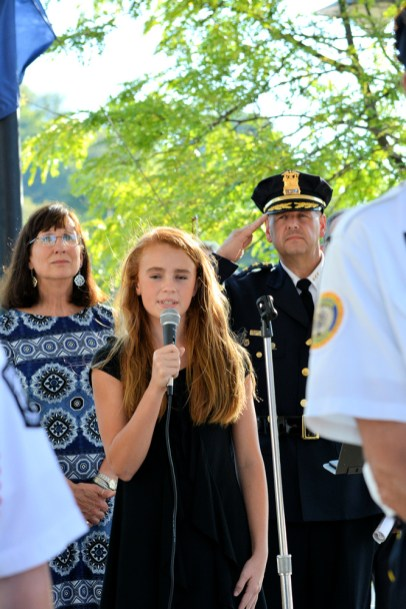 Adriana Vicianzo sings the National Anthem. Mayor Ann Thane, Police Chief Greg Culick are in the background. Photo by Robert Fiore, used by permission.