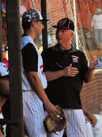 Head Coach Keith Griffin, right, talks to one of the Amsterdam players between innings.