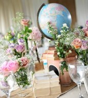 Vintage bookstacks used as part of a centerpeice, with our vintage globe - all surrounded by pretty flowers in bottles