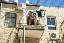 A Haredi child looks down from a balcony in the Bea Shearim neighborhood of Jerusalem. The number of children in a Haredi household is nearly double the average Jewish household, an average of 3.86 compared to 1.99 according to the Taub Center for Social Policy Studies in Israel. Photo: Gustavo Martínez Contreras|30 May 2016
