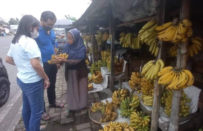 Mbah Manto melayani pembeli pisang di lapaknya depan RS Grahasia, Pakem. Foto oleh Agung PW/Mojok.co
