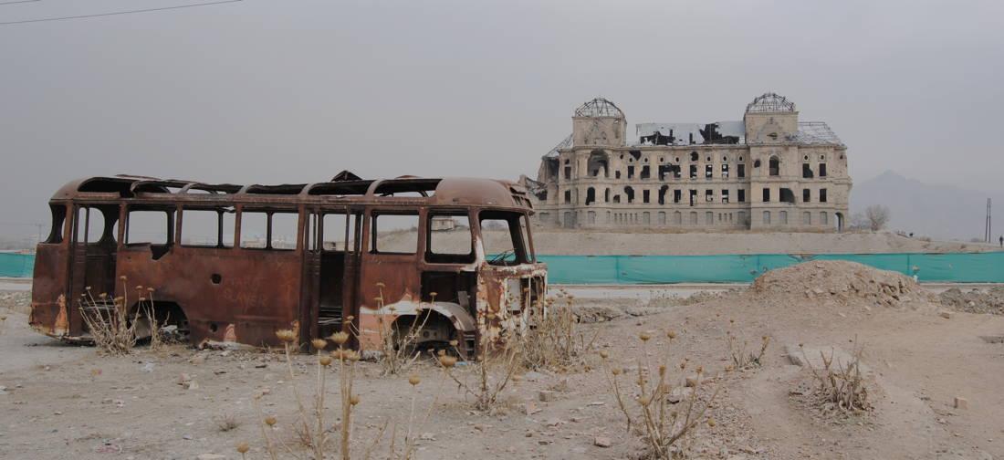 uitgebrande bus en gebombardeerd gebouw