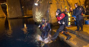 Gary Burger and Jim Mondl jump into the water at Bonne Terre Mine Lake in Bonne Terre, Mo. with fellow attorney Sharon Cody standing by.  The three attorneys serve as diving guides and instructors at the lake.  Photo By: KAREN ELSHOUT