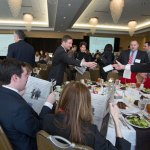 Assistant U.S. attorneys find their table at the luncheon honoring them as well as the other Lawyers of the Year at the Ballpark Hilton.  The Missouri Lawyers Weekly annual event celebrates the accomplishments in the legal profession.  Seated is Richard Finneran, as Steven Muchnick reaches over to get his seat assignment from Charles Birmingham.  The three were honored for their work on the funeral fraud case.