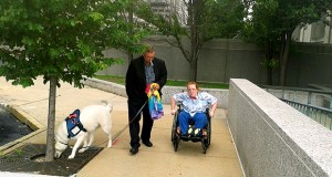 Maddison Schmidt, 12, leaves the St. Louis Civil Courts Building with her grandfather, Gary Schmidt, and service dog, Paws, during a break in a trial over Depakote.  Plaintiff's attorneys claim the anti-seizure medicine caused birth defects that led to Maddison's physical disabilities and intellectual challenges. Photo by Heather Cole