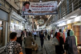 People walk at the old main bazaar in Tehran, Iran. The most-visible place to see the effect of the economic hardship most face comes from walking by any money-exchange shop. As the U.S. piles sanction after sanction on Iran, it's the average person who feels it the most. At the time of the nuclear deal, Iran's currency traded at 32,000 rials to $1. Today, it costs over 130,000 rials for one U.S. dollar. AP Photo by Ebrahim Noroozi