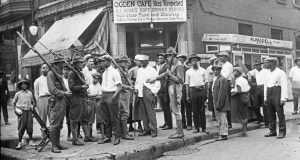 In this 1919 photo provided by Chicago History Museum, a crowd of men and armed National Guard stand in front of the Ogden Cafe during race riots in Chicago. Red Summer, as the summer of 1919 came to be known, saw white-on-black violence in big cities like Washington and Chicago and small towns like Elaine, Ark., and Bisbee, Ariz. (Chicago History Museum/The Jun Fujita negatives collection via AP)