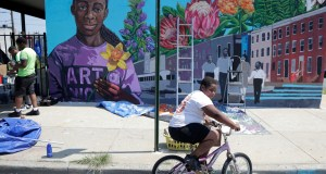 """A boy rides his bicycle after volunteering to paint a mural outside the New Song Community Church in the Sandtown section of Baltimore. In the latest rhetorical shot at lawmakers of color, President Donald Trump over the weekend vilified Rep. Elijah Cummings majority-black Baltimore district as a """"disgusting, rat and rodent infested mess"""" where """"no human being would want to live."""" AP Photo by Julio Cortez"""