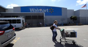 A customer pushes a shopping cart outside a Walmart store, in Walpole, Mass. Walmart is going back to its folksy hunting heritage and getting rid of anything that's not related to a hunting rifle after two mass shootings in its stores in one week left 24 people dead in August of 2019. AP Photo by Steven Senne