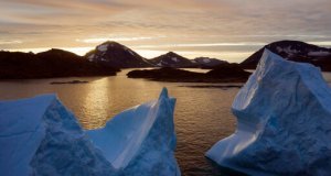 FILE - This Aug. 16, 2019 file photo shows an aerial view of large icebergs floating as the sun rises near Kulusuk, Greenland. A special United Nations-affiliated oceans and ice report released on Sept. 24, 2019 projects three feet of rising seas by the end of the century, much fewer fish, weakening ocean currents, even less snow and ice, and nastier hurricanes, caused by climate change. (AP Photo/Felipe Dana)