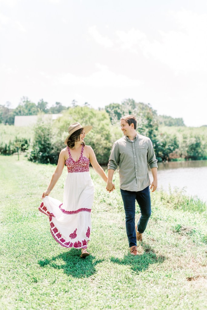photo of couple walking by the water