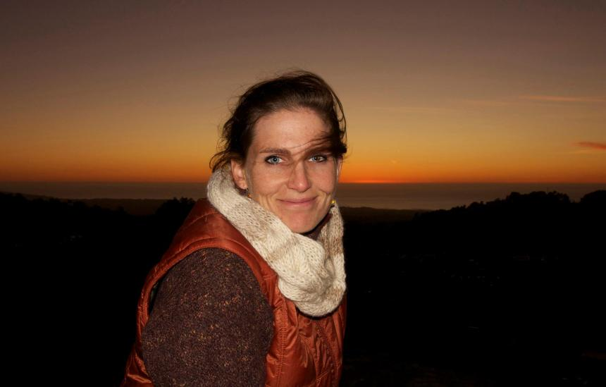 Photo of a white woman with wind blown hair, wearing a scarf. The sun is setting on the ocean behind her.