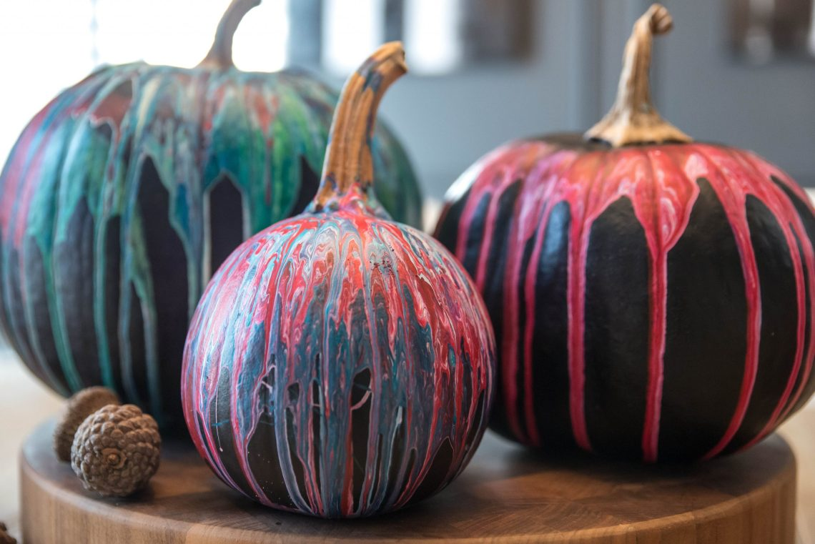 Fun pumpkin painting idea - Pumpkins painted in black chalk paint with colorful paint poured all over