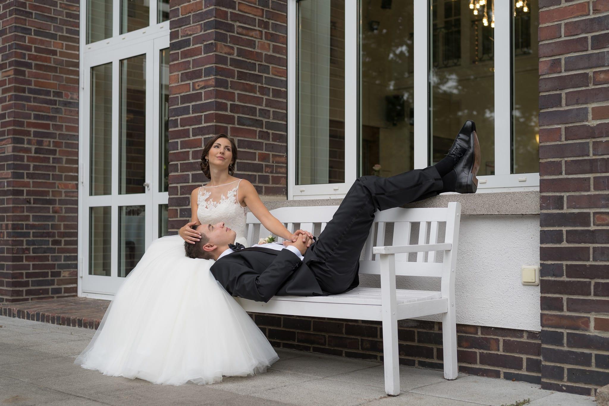 Brautpaar entspannt auf Bank vor Festsaal