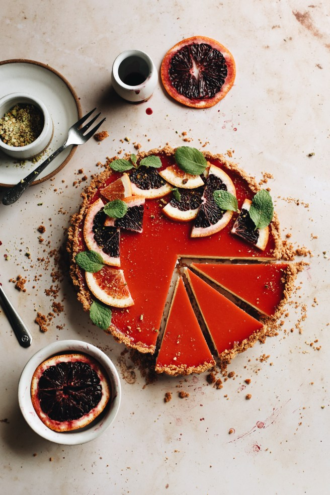 blood orange cheesecake tart, with slices cut out to show the inside texture