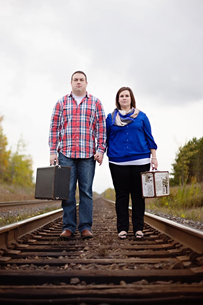 Cornwall engagement session - couple standing on train track with suitcases