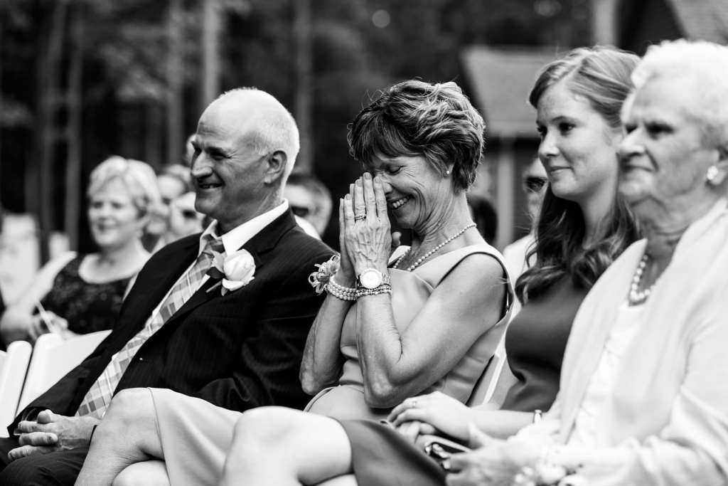 woman laughs with hands in front of face during Cornwall wedding ceremony