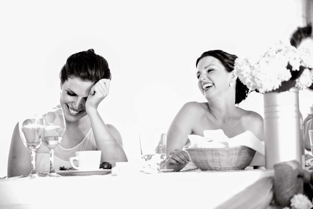 two women laughing while one holds head in hands during Cornwall wedding