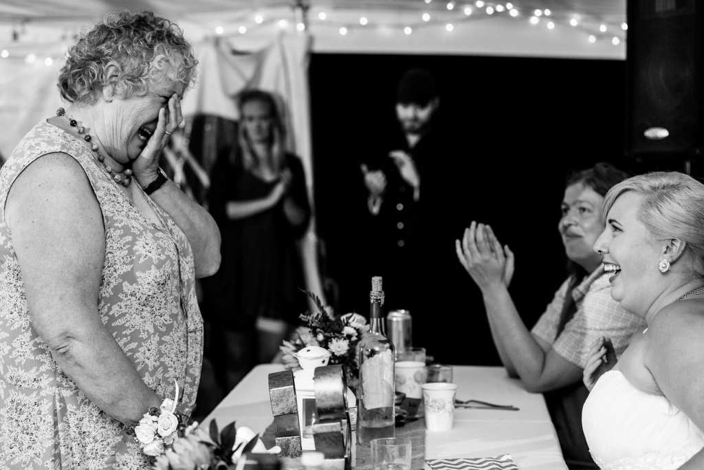 woman holding face and crying in front of brides at Cornwall wedding