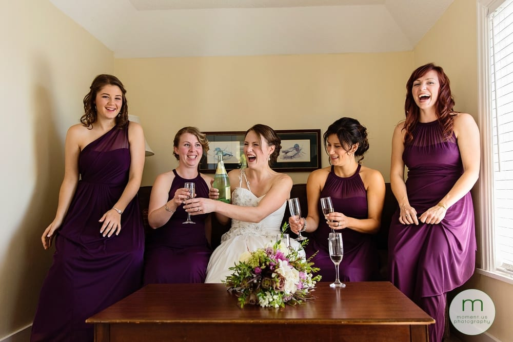 bride laughing with bridesmaids on couch