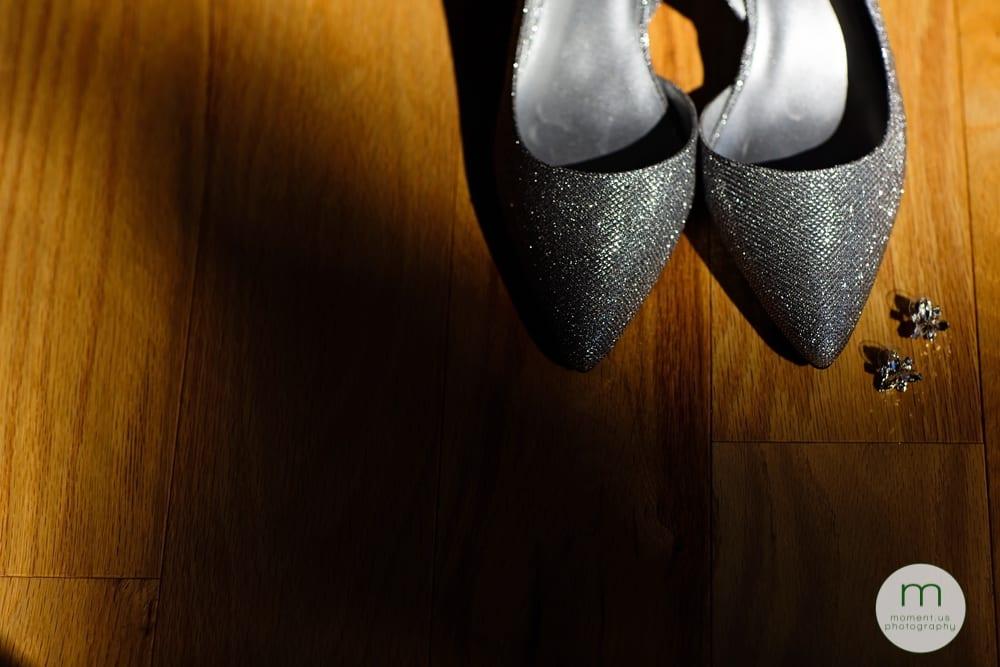 bride's shoes and earrings on hardwood floor