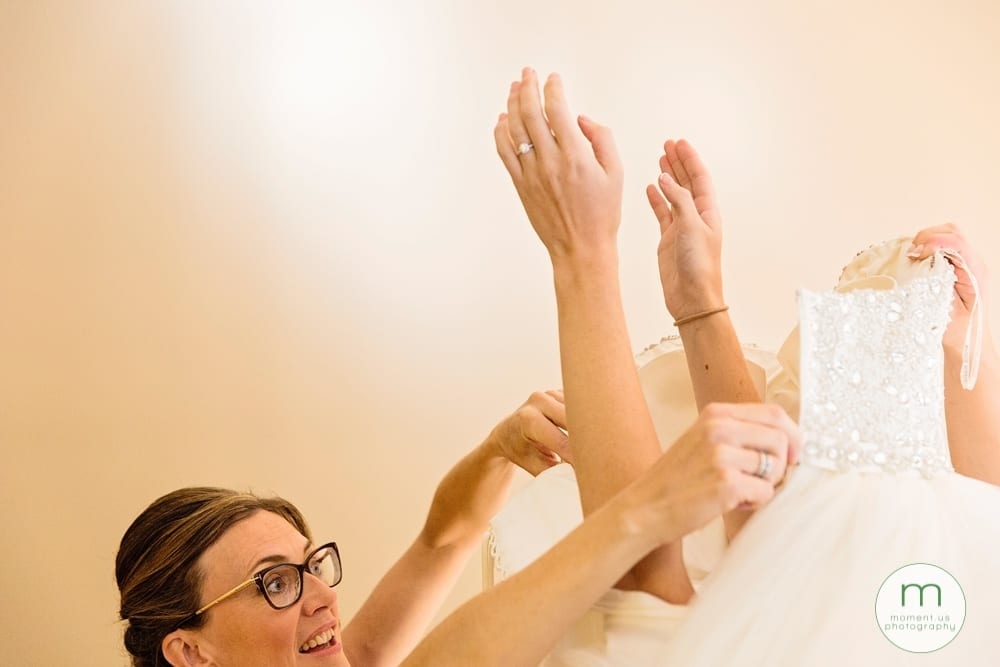 bride putting arms through dress