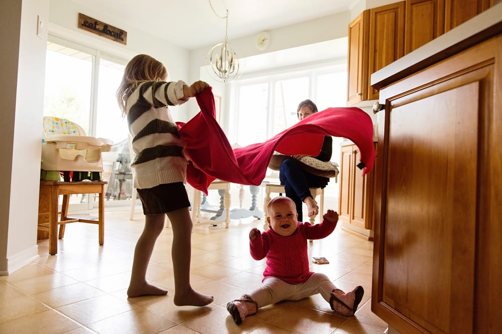 Cornwall family photographer - sisters playing with blanket in kitchen
