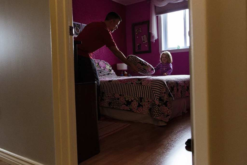 dad and daughter making bed during shoot for family photography in cornwall