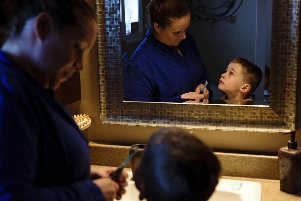mom helping son brush teeth