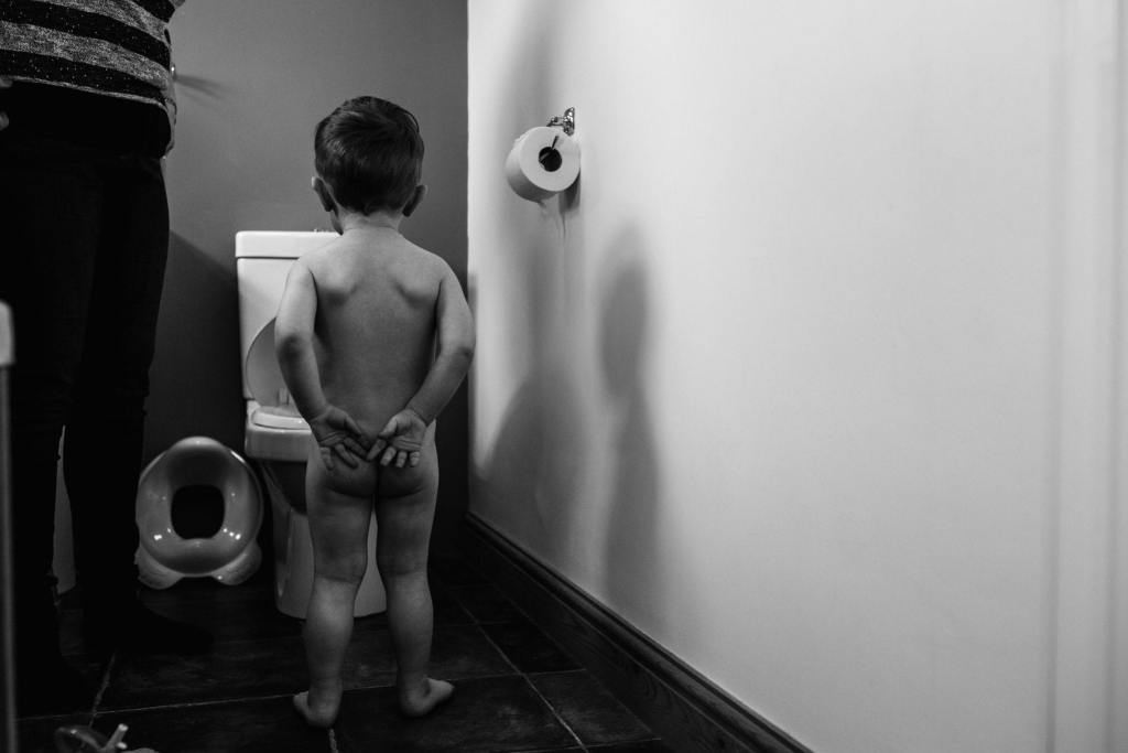 boy looking at toilet during South Wales family session