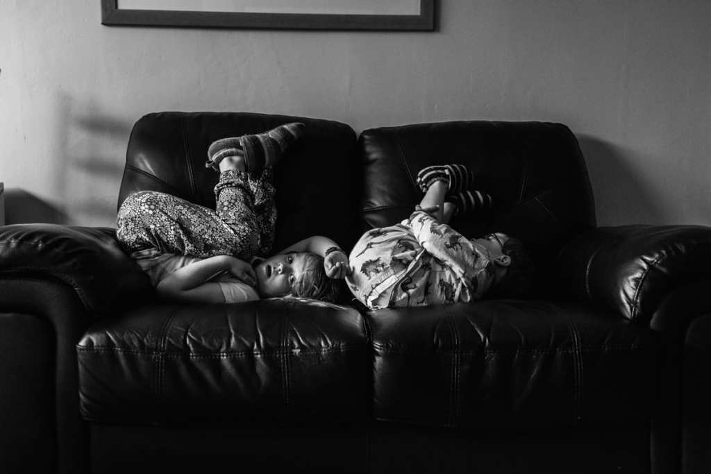 brother and sister playing on couch during London family photography session