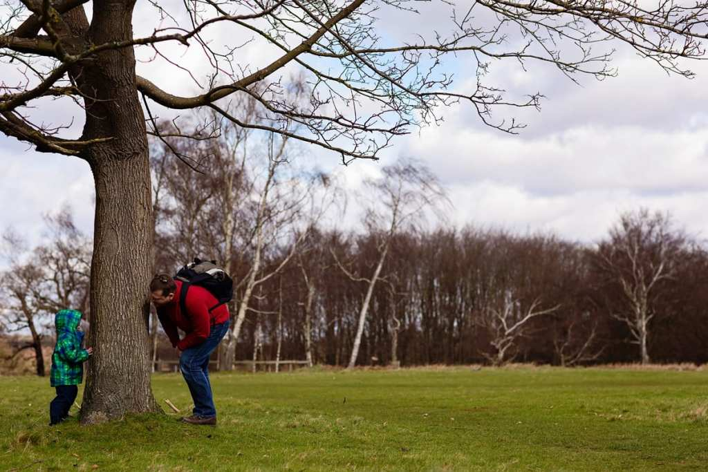 Father and son playing by tree during London family photography session