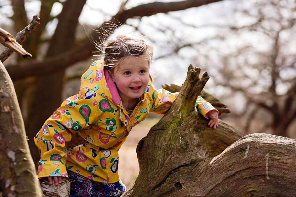 Girl playing on tree trunk during London family photography session