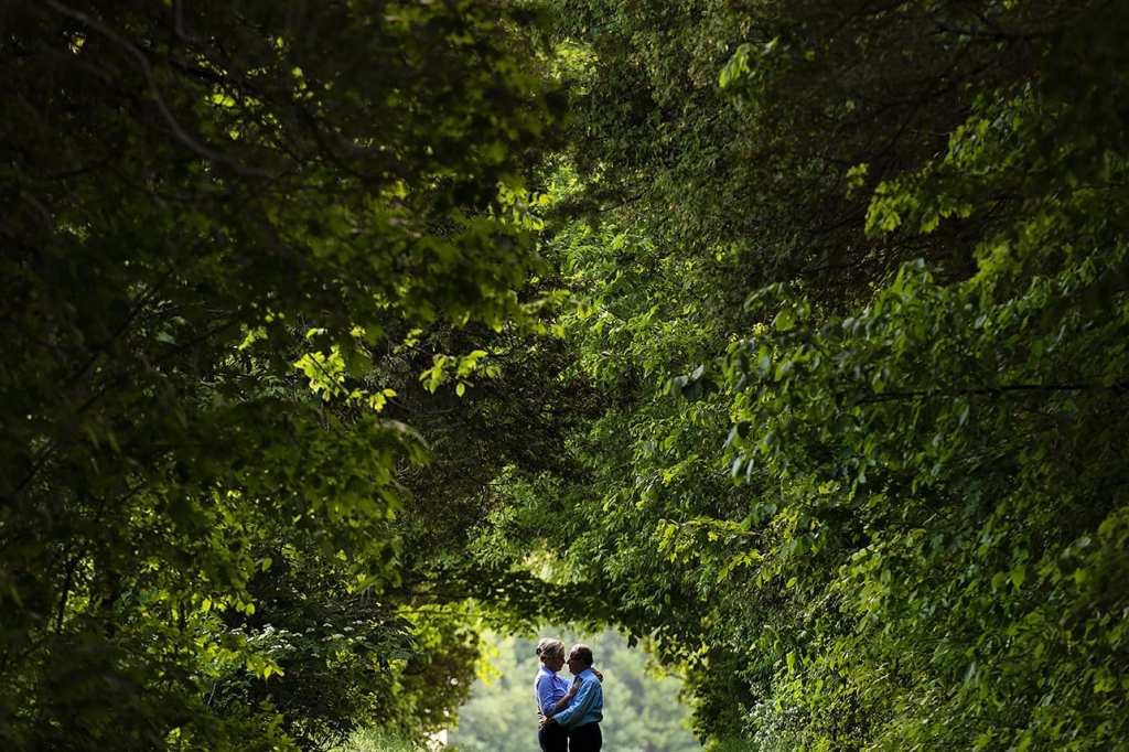 Couple standing together in tree tunnel