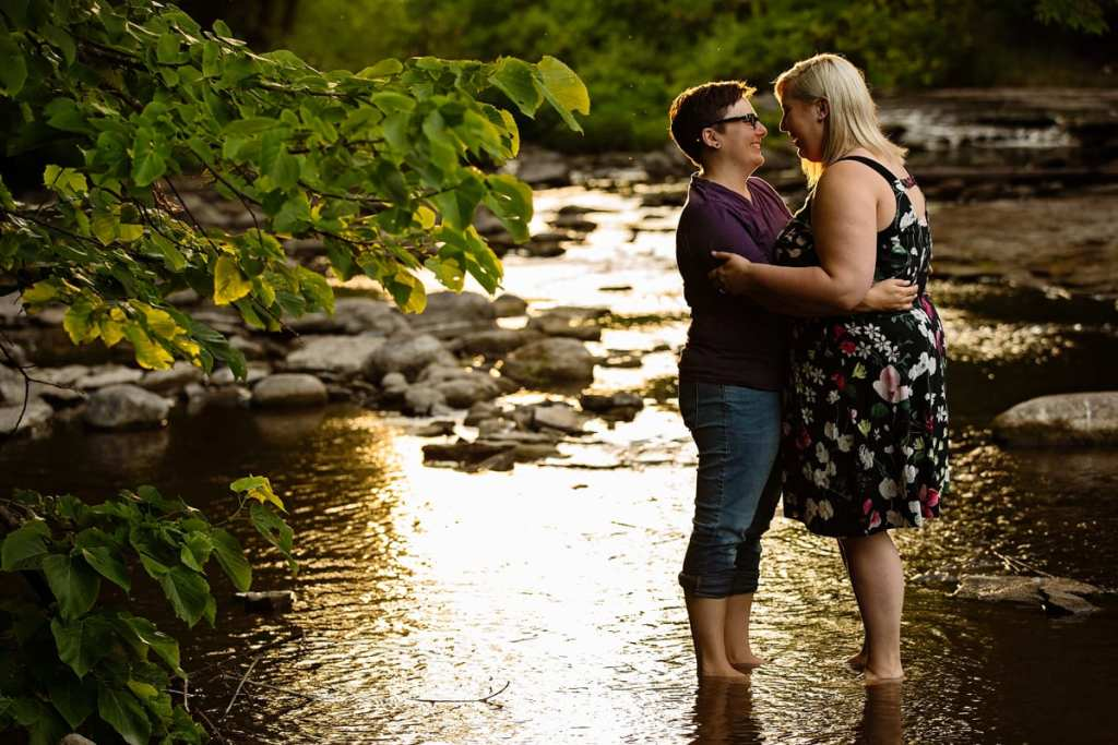 Women embracing in shallow river at sunset
