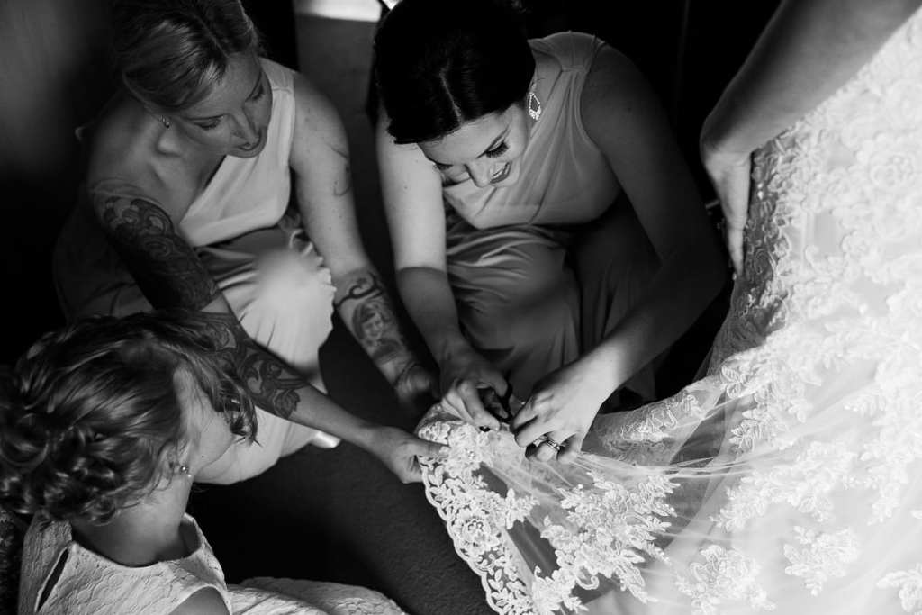 Bridesmaids helping bride with wedding gown and getting ready