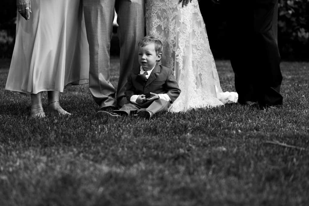 Ring bearer sitting at feet of wedding party