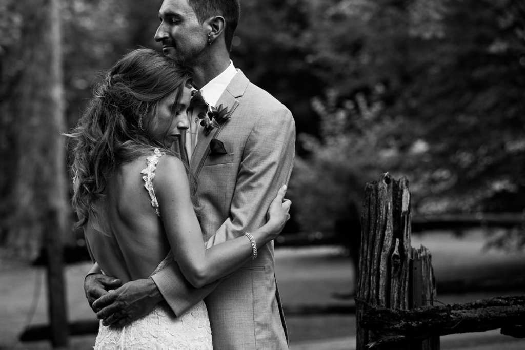 Bride ad groom embracing beside rustic wooden fence at intimate Strathmere wedding