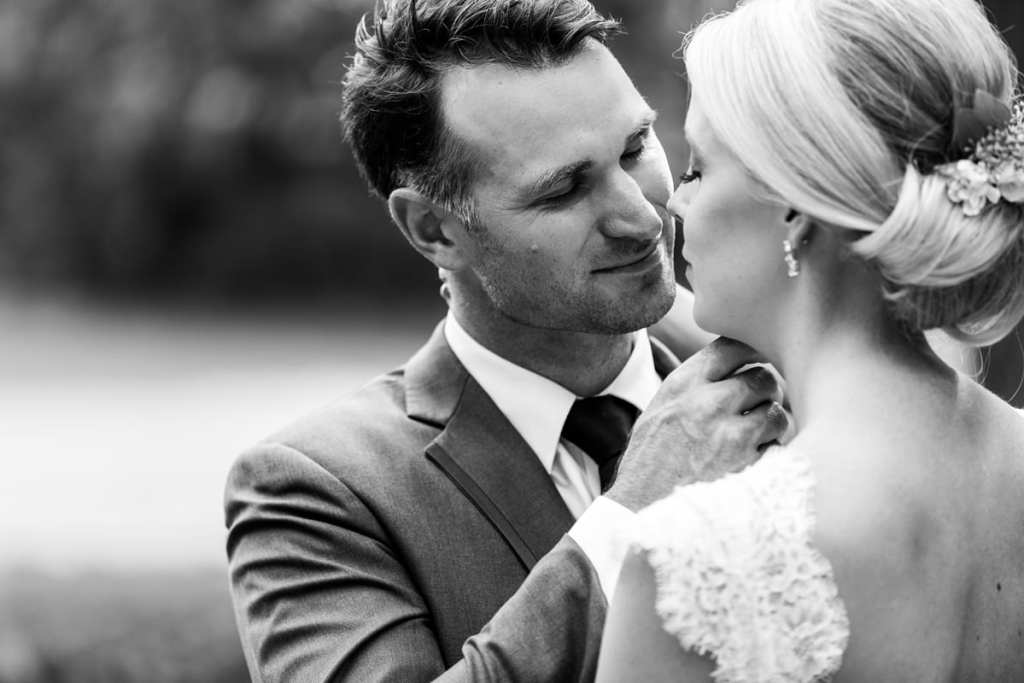 Groom gently touching bride's face in rural backyard wedding
