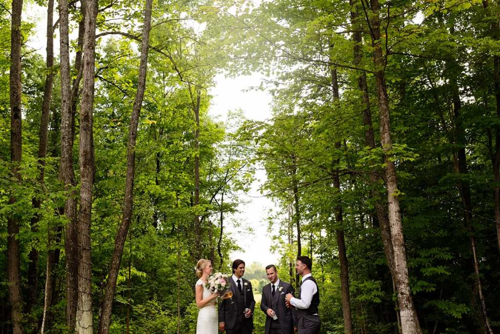 Bride and groom with best man and usher having drinks in wooded area