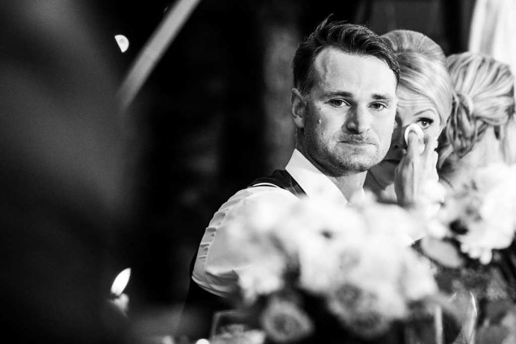 Emotional bride and groom at head table