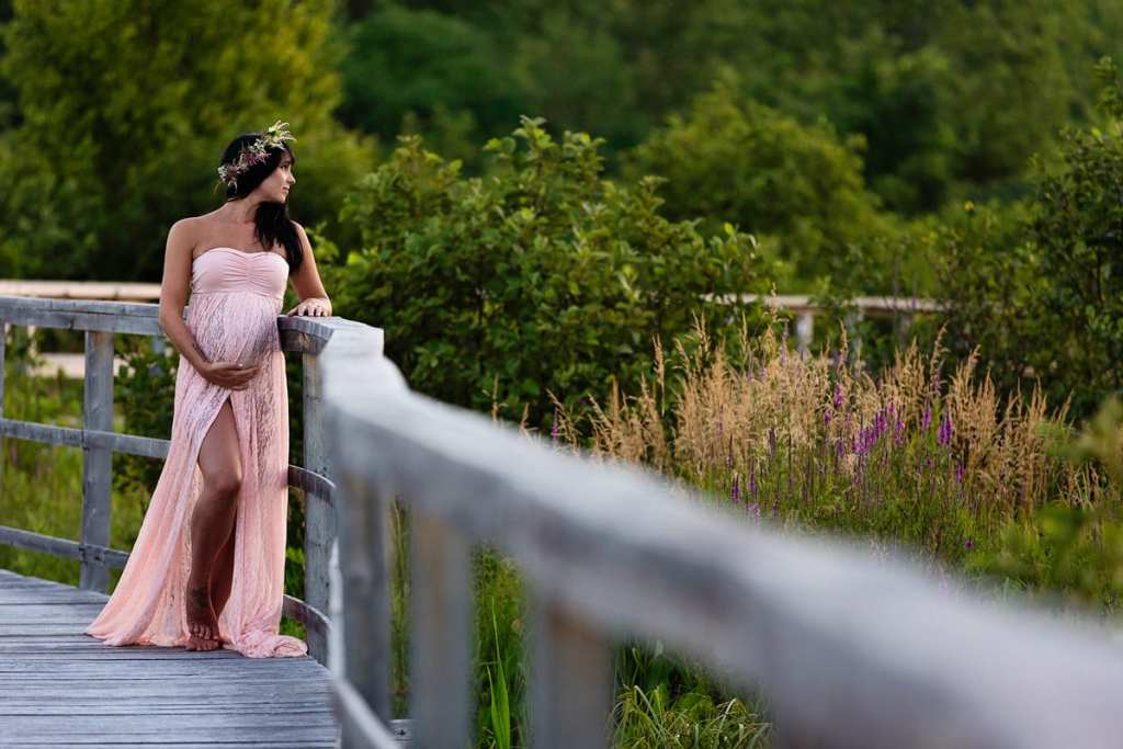Expectant mom in blush dress on wooden boardwalk