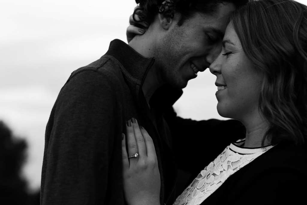 Woman with hand on man's chest in modern Cornwall engagement shoot