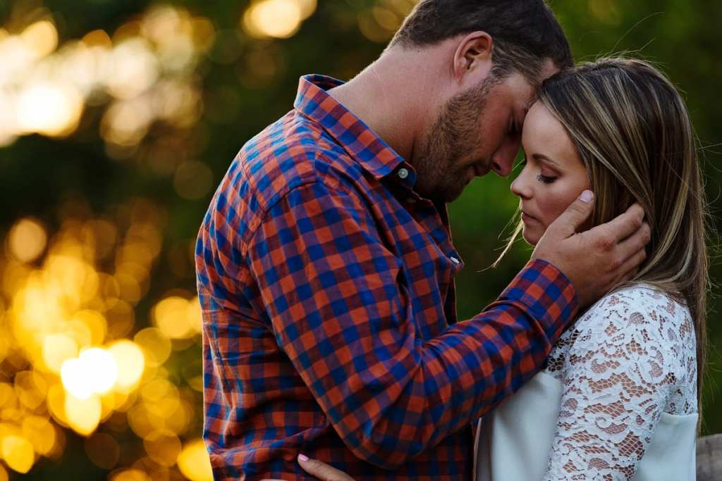 Man in plaid shirt gently holding fiancee's face